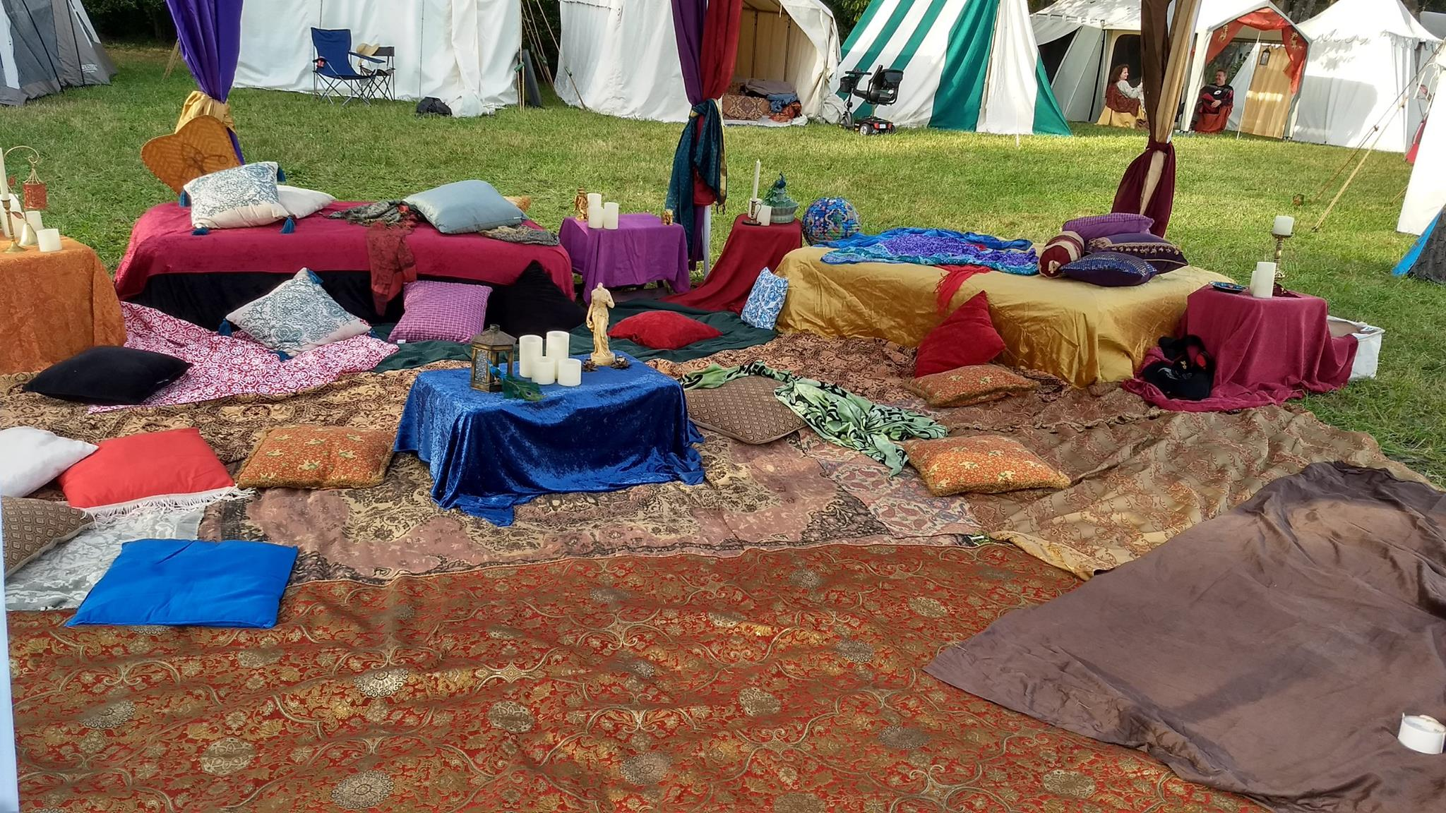 A large white canopy tent, under which are rugs, cushions, beds, and tables all covered with luxurious fabrics and fake candles
