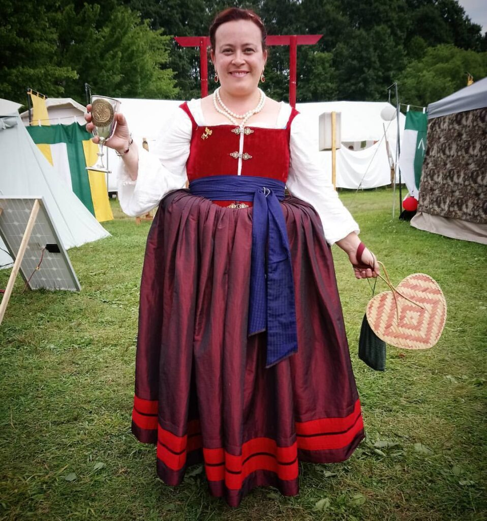 A woman dressed in Renaissance clothing smiling and holding a wine glass, a fan, and a purse