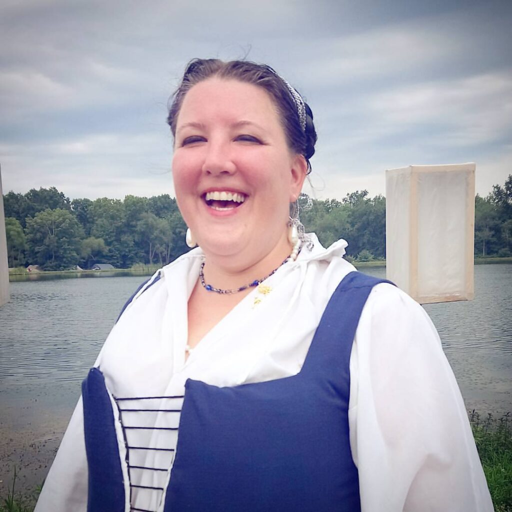 A woman dressed in Renaissance clothing smiling with a lake in the background