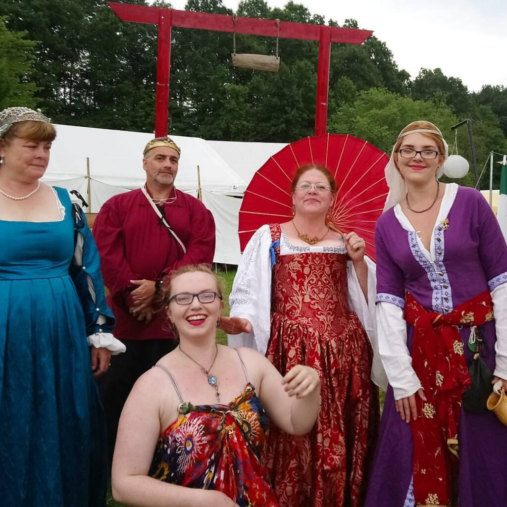 Five people wearing medieval and Renaissance clothing posing together