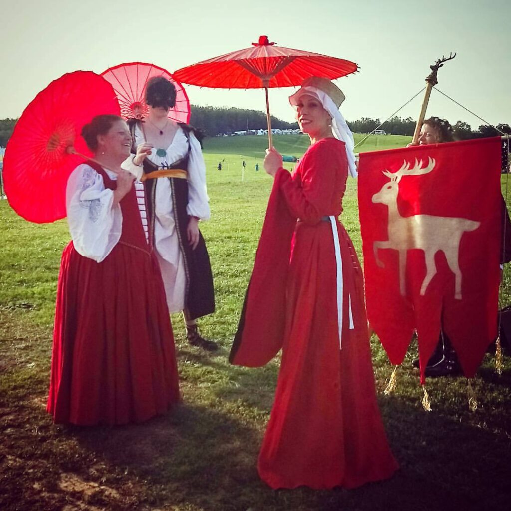 4 women dressed in medieval and Renaissance clothing stand on a grassy hill, three carry red parasols and the fourth carries a red banner with a gold stag