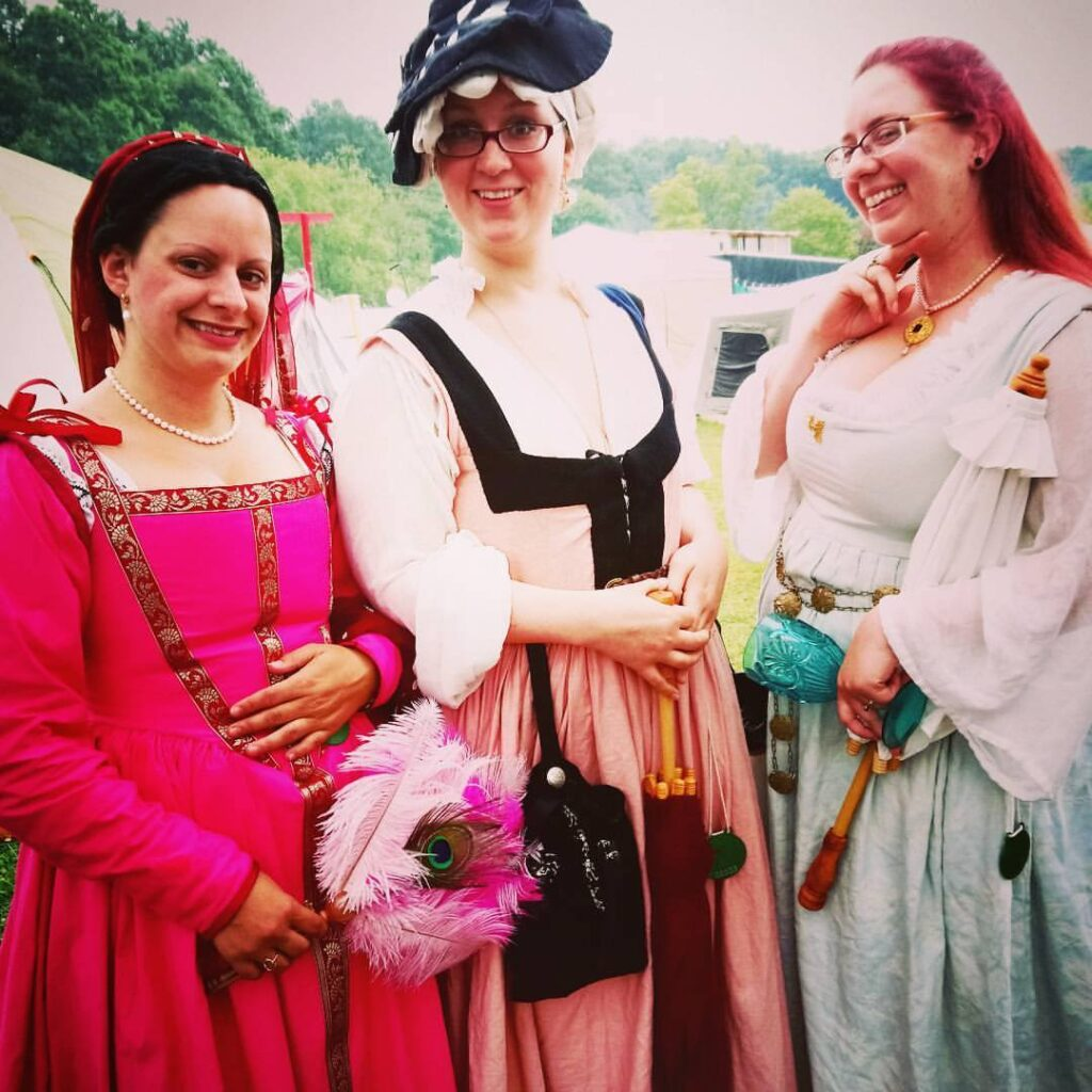 Three courtesans wearing Renaissance clothing posing together