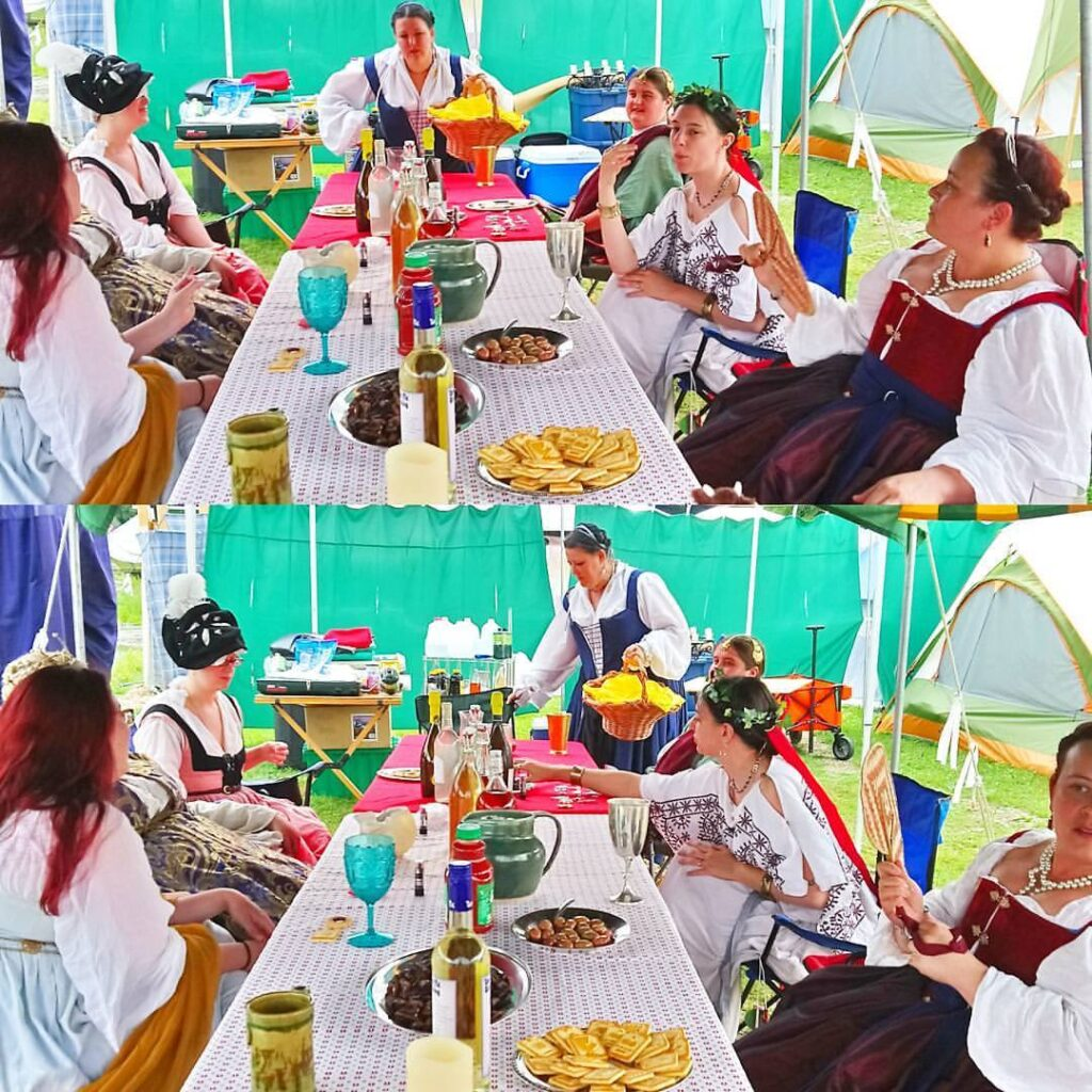 7 people dressed in ancient Roman, medieval, and Renaissance clothing sitting around a table eating and talking