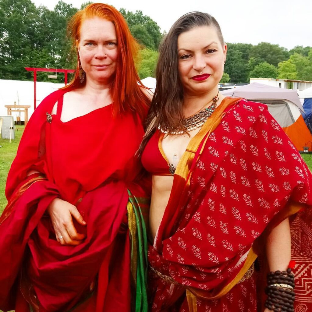 Two courtesans posing together, one wearing ancient Roman clothing, the other wearing Indian clothing