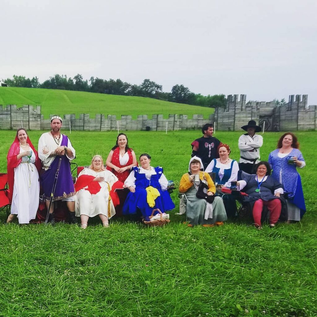 11 people dressed in ancient Roman, medieval, and Renaissance clothing sitting and standing in a group photo on a grassy hill with a wooden fort in the background