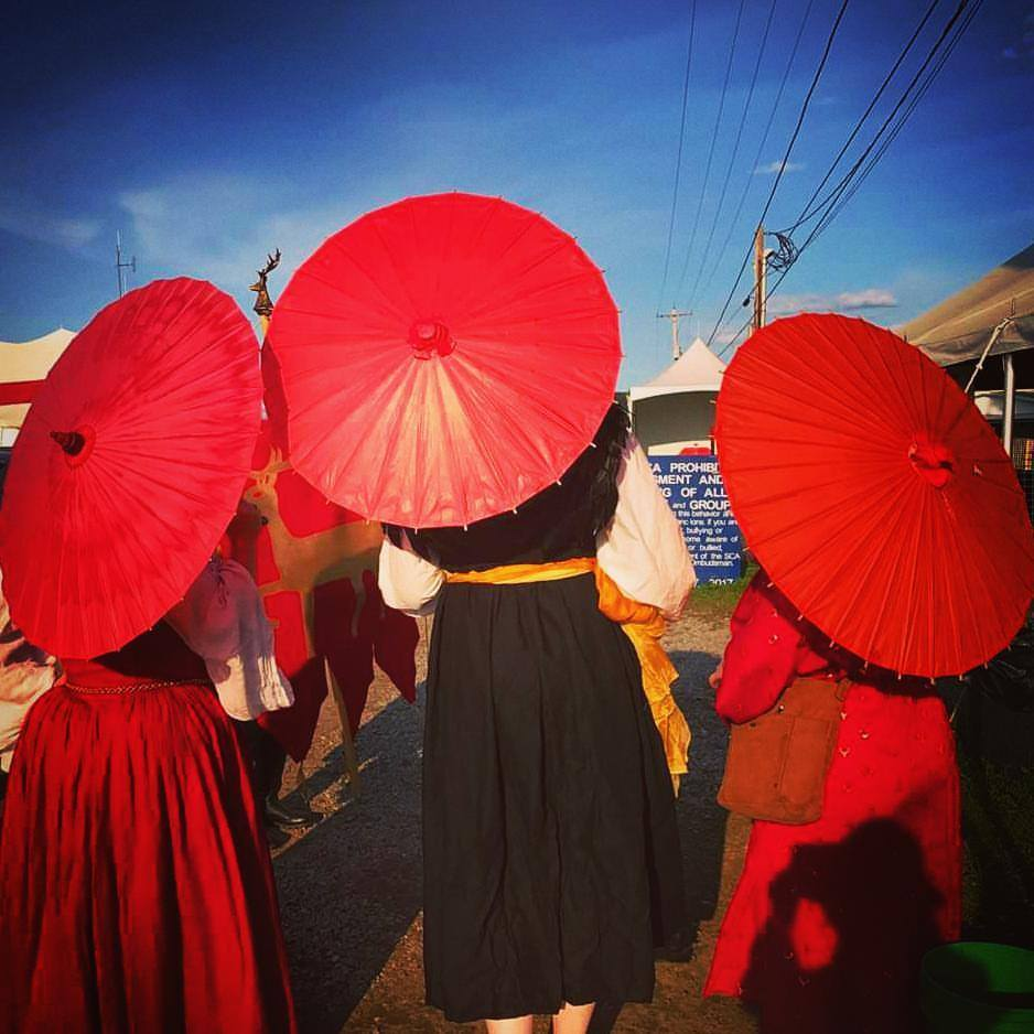 3 women dressed in ancient Roman and Renaissance clothing stand facing away from the camera, carrying red parasols