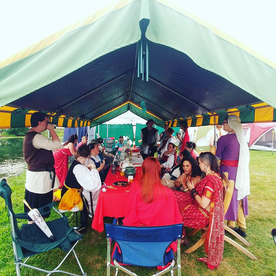 A group of people wearing ancient Roman, medieval, and Renaissance clothing sitting around a table under a large canopy eating and talking