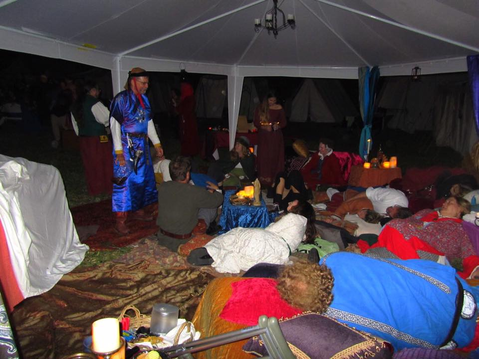 A group of people in ancient Roman, medieval, and Renaissance clothing lounging and standing under a large white canopy on top of cushions and rugs lit by fake candles