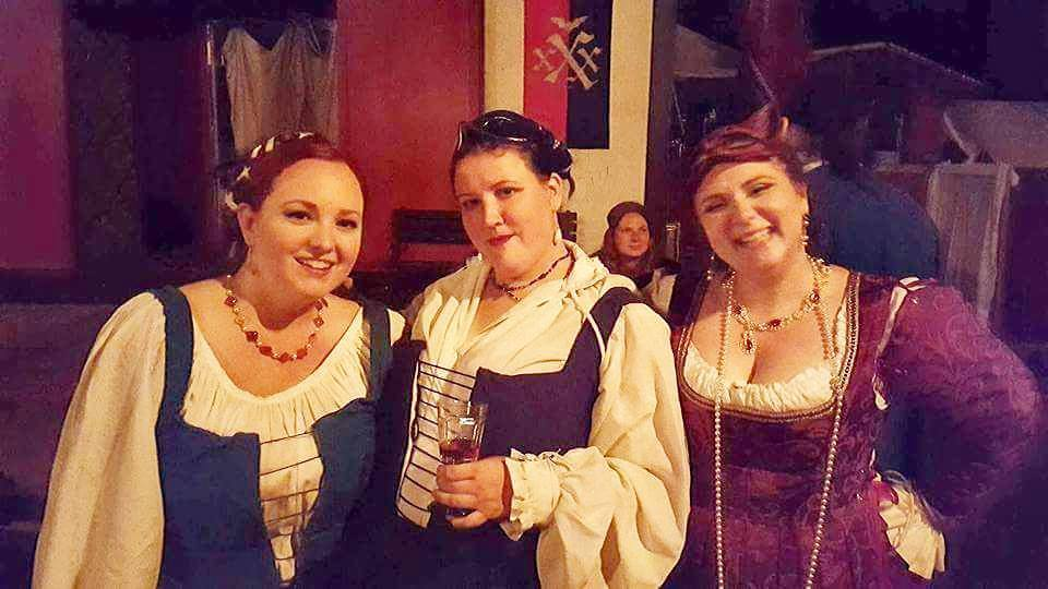 3 women dressed in Renaissance clothing posing together which medieval style shops in the background