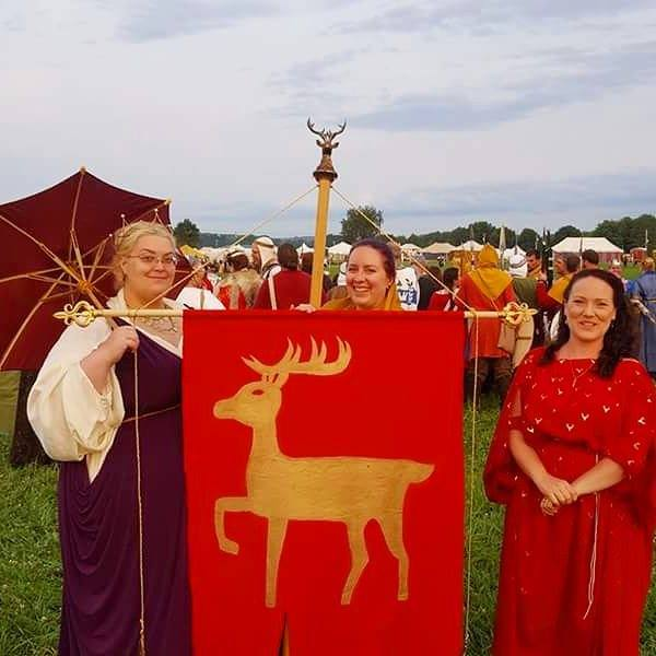 3 women dressed in ancient Roman clothing stand on a grassy hill with a crowd of reenactors in the background, one carries a red parasol and two support a red banner with a gold stag