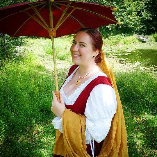 A woman dressed in Renaissance clothing and a yellow veil smiling and holding a red parasol
