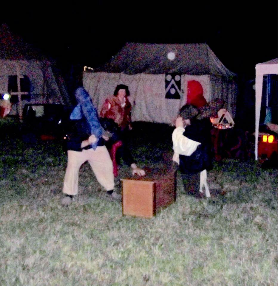At night, 2 blindfolded people in medieval clothing circle each other around a wooden chest holding large fish-shaped pillows while a third person referees
