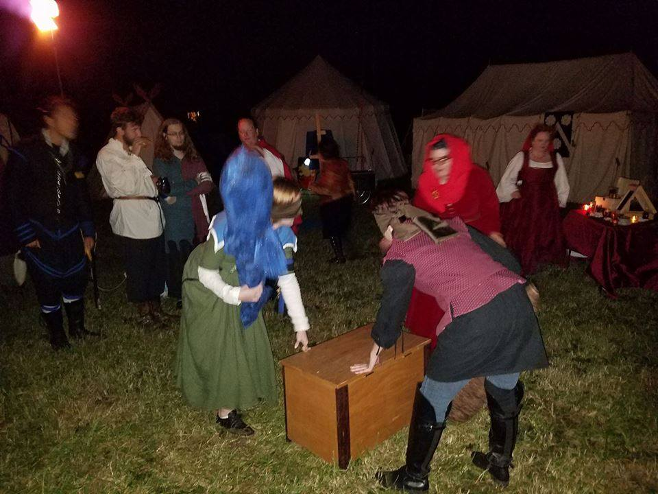 At night, 2 blindfolded people in medieval clothing circle each other around a wooden chest holding large fish-shaped pillows while others watch