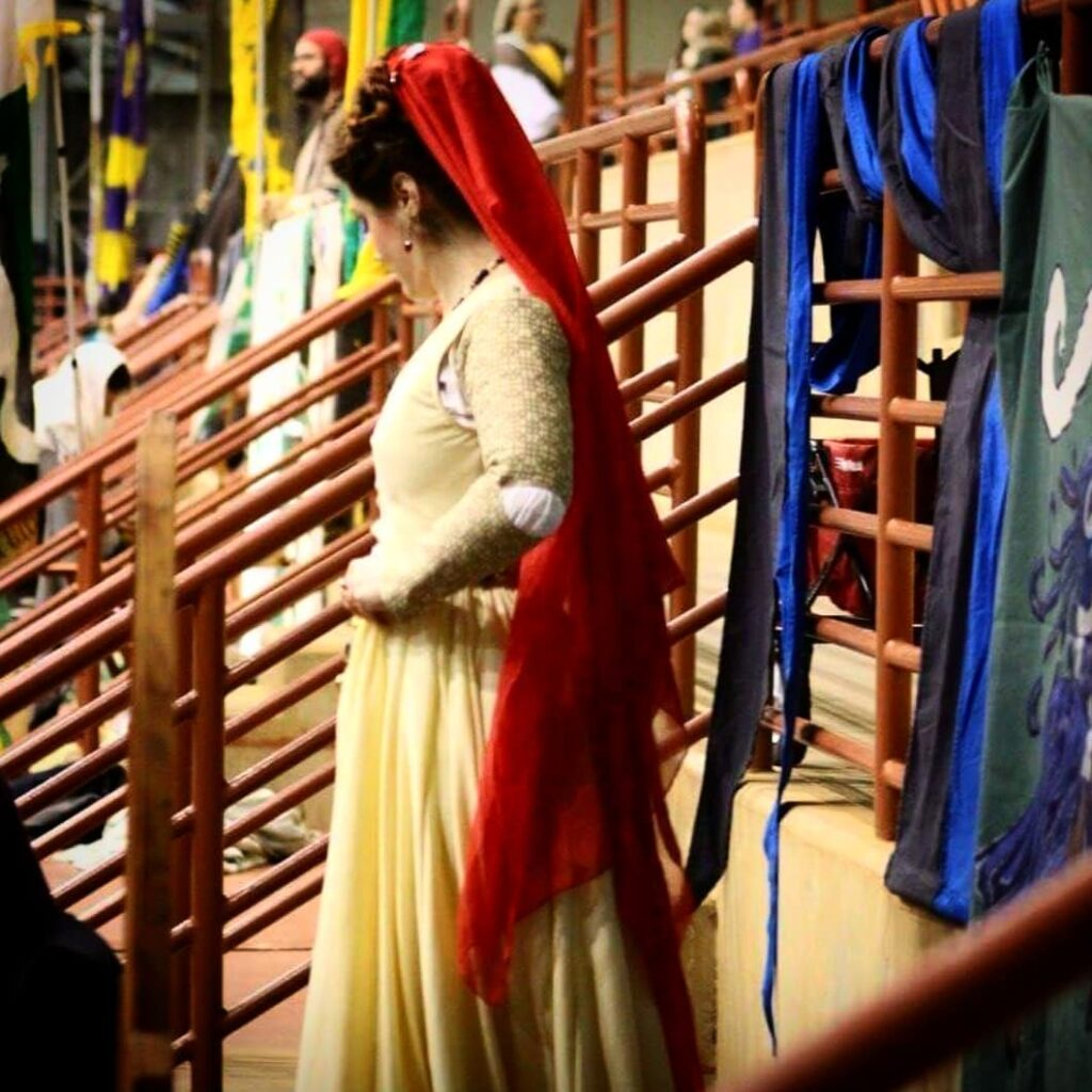 A woman dressed in Renaissance clothing and a red veil looking away from the camera