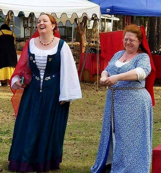 2 women wearing red veils, one wearing Renaissance clothing, the other wearing Persian clothing, stand next to each other smiling with tents in the background