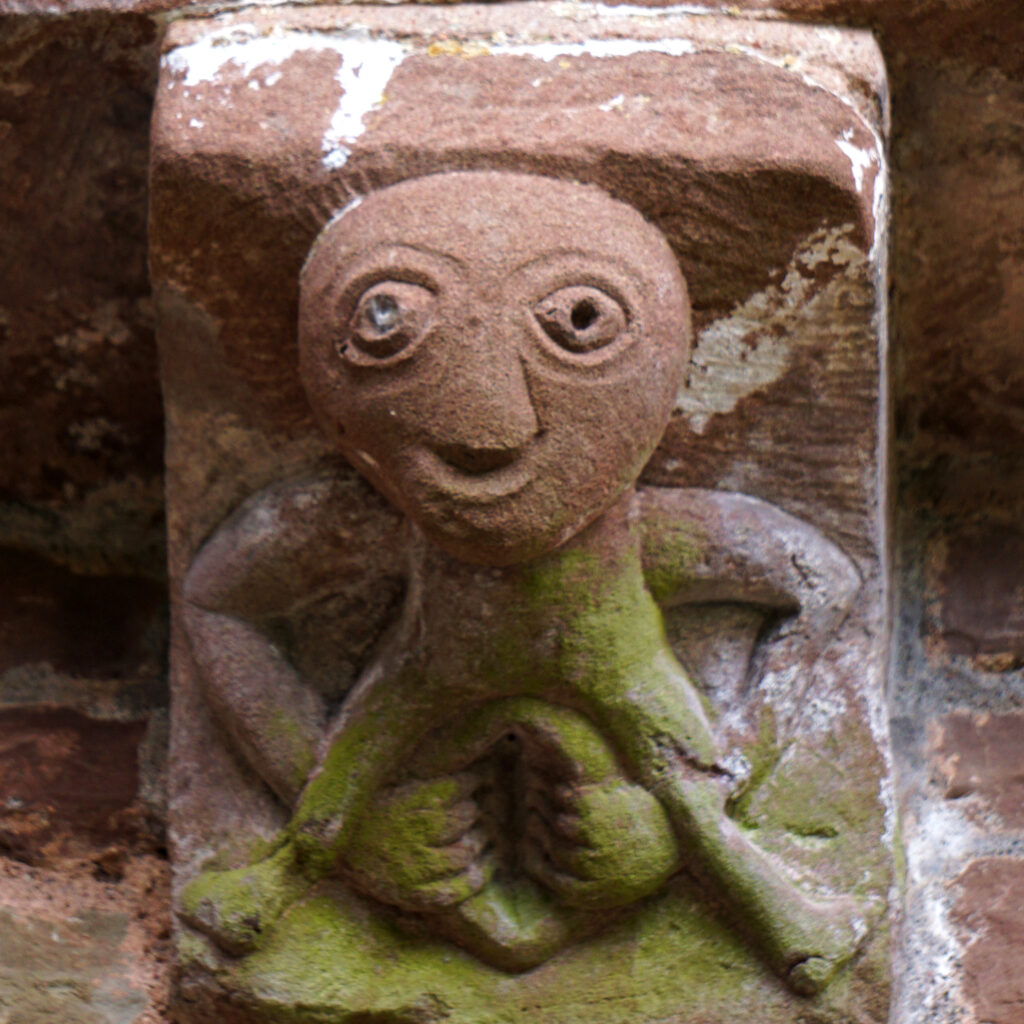 A crude stone carving of a human figure reaching down to spread an oversize vagina